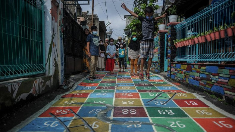 Sejumlah anak bermain permainan ular tangga di Jalan Asep Berlian, Gang Wargaluyu, Cibeunying Kidul, Bandung Jawa Barat, Rabu (3/3/2021). Pengurus RW dan warga setempat berinisiatif untuk membuat permainan tradisional bagi anak melalui karya seni mural guna mengantisipasi anak kecanduan gawai di masa pembelajaran jarak jauh selama pandemi COVID-19. ANTARA FOTO/Raisan Al Farisi/hp.