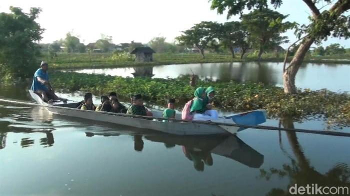 Banjir yang merendam kawasan Lamongan, Jawa Timur, membuat sejumlah jalan sulit diakses. Akibatnya, para pelajar menggunakan perahu saat berangkat ke sekolah.