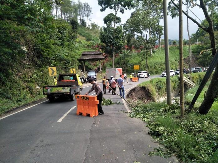 Bahu Jalan Brigjen Abdul Manan di Desa Ngroto, Kecamatan Pujon, Kabupaten Malang ambles. Bahu jalan tersebut tergerus air Sungai Konto yang mengalir di sisi timur jalan.