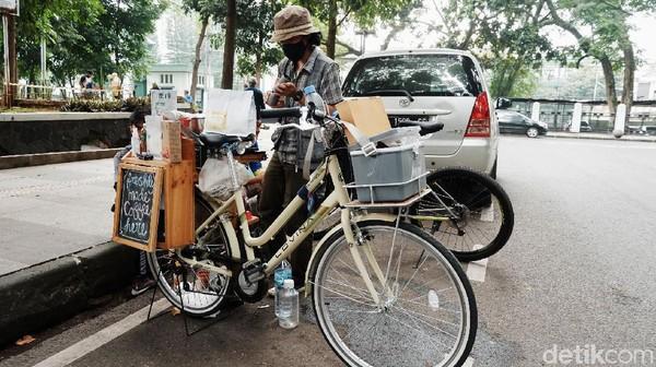 Angga Gilang Ramadhan menjual kopi keliling menggunakan sepeda di kawasan Lapangan GOR Saparua, Kota Bandung.