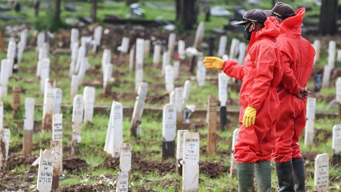 Petugas berjalan di areal pemakaman khusus dengan protokol COVID-19 di TPU Bambu Apus, Jakarta Timur, Selasa (2/3/2021). Menurut Kepala Dinas Pertamanan dan Hutan Kota Provinsi DKI Jakarta Suzi Marsitawati, dua blok atau blad TPU Bambu Apus telah penuh terisi oleh 1.050 jenazah yang meninggal dunia akibat menderita COVID-19. ANTARA FOTO/M Risyal Hidayat/wsj.