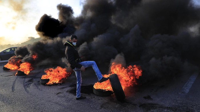 Protesters ride a scooter past burning tires set on fire to block a highway that leads to Beirut's international airport, in Beirut, Lebanon, Tuesday, March 2, 2021. Scattered protests broke out in different parts of Lebanon Tuesday after the Lebanese pound hit a record low against the dollar on the black market, a sign of the country's multiple crises deepening with no prospects for a new Cabinet in the near future. (AP Photo/Hussein Malla)