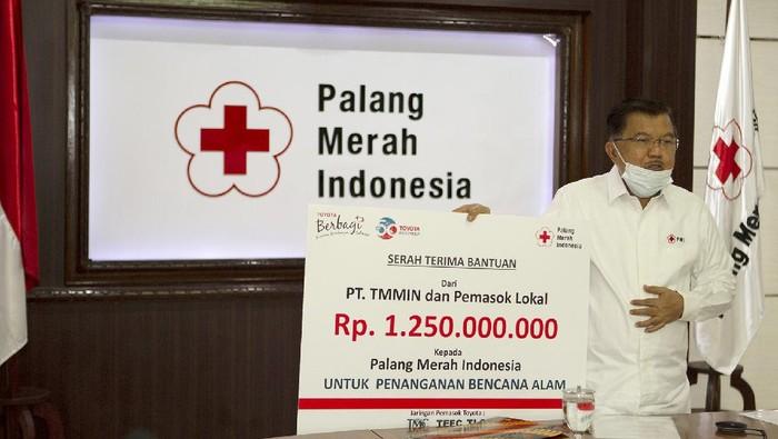 Ketua Umum Palang Merah Indonesia (PMI) Jusuf Kalla memperlihatkan plakat simbolis bantuan penanganan bencana alam dari PT Toyota Motor Manufacturing Indonesia (TMMIN) dan perusahaan pemasok lokal Toyota yang tergabung dalam Toyota Manufacturers Club (TMClub),  Toyota Logistic Community (TLC), dan Toyota Equipment and Facility Community (TEFC) kepada PMI Pusat senilai Rp 1,25 miliar yang diserahkan oleh Presiden Direktur TMMIN Warih Andang Tjahjono pada acara serah terima secara daring dan sesuai standar protokol kesehatan selama pandemi COVID-19 di Markas Pusat PMI dan TMMIN Head Office Jakarta, Selasa (2/3).
