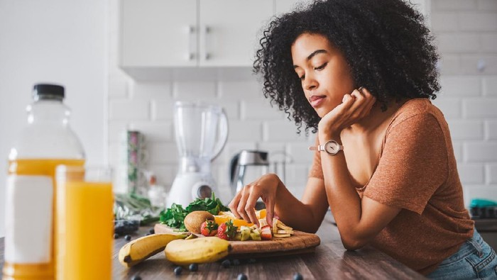 Shot of a young woman looking unhappy while making a healthy snack with fruit at home