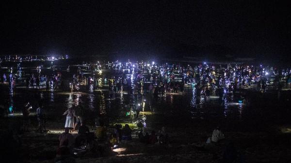 Kegiatan berburu cacing laut warna-warni itu pun terus berlangsung meski matahari telah tenggelam. Sebagai pengganti cahaya, warga menggunakan lampu dari senter maupun kamera ponsel.
