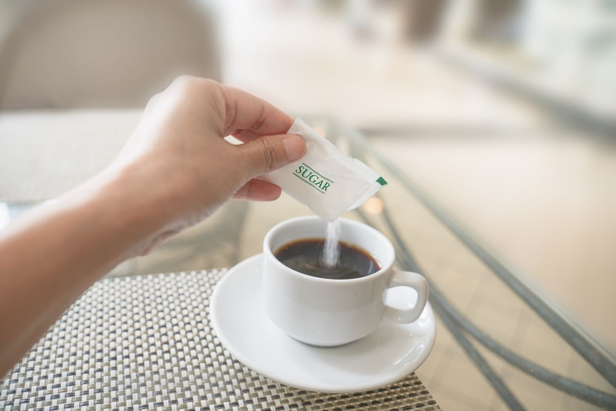 human hand with white sugar packet and pouring in hot black coffee , in soft focus