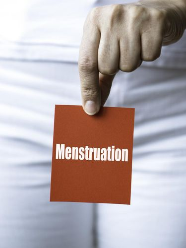 Torso of an unrecognizable woman is showing red square card to camera representing with menstruation written in white.
