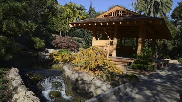 Paviliun terbuka, dibangun di samping air terjun, menawarkan ruang damai untuk rileksasi dan meditasi dengan pemandangan pasir, bebatuan, dan bebatuan taman kering, dengan kolam reflektif dan hamparan taman luas di luarnya.