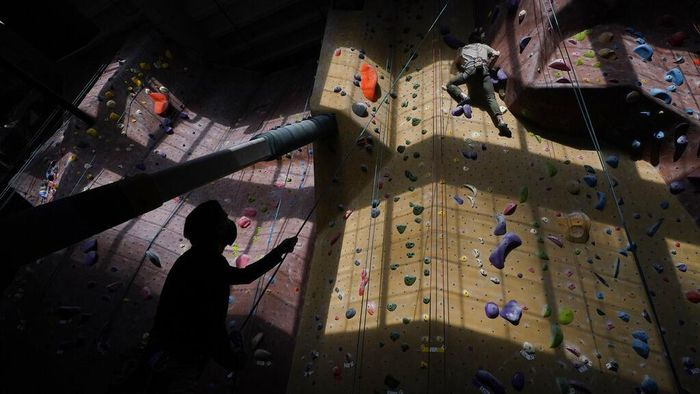 Audrey Grochowski, left, and Sam Masters wear protective face masks while working out at Planet Granite climbing gym during the coronavirus pandemic in San Francisco, Thursday, March 4, 2021. The gym opened today to allow ten percent capacity. (AP Photo/Jeff Chiu)