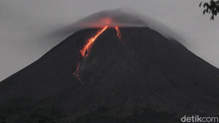 Gunung Merapi dengan awan lentikular (awan topi) di bagian atas mengeluarkan lava pijar terlihat dari Turi, Sleman, Yogyakarta, Jumat (5/3/2021). Berdasarkan pengamatan BPPTKG, pada pukul 18.00 tanggal 4 Maret 2021 hingga pukul 06.00 tanggal 5 Maret 2021. Gunung Merapi mengeluarkan lava pijar sebanyak 81 kali, dengan jarak luncur maksimal 1.200 meter ke arah barat daya.
