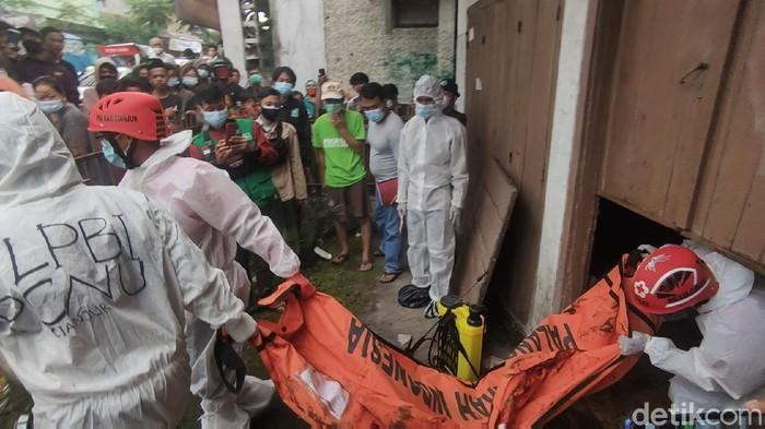 Petugas evakuasi jenazah kakak dik yang ditemukan tewas di dalam rumahnya