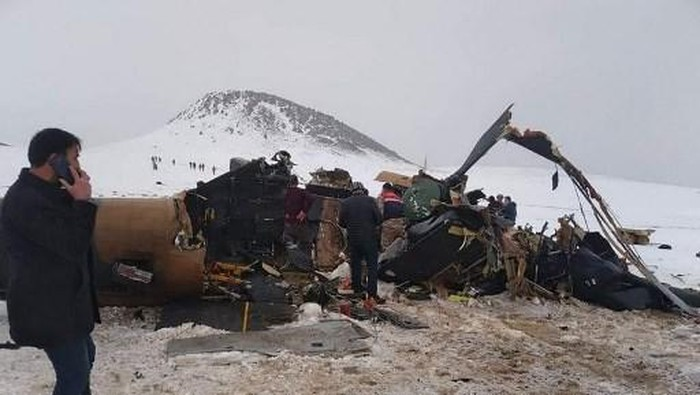 Rescue workers, soldiers and civilians walk around the wreckage of a military helicopter that crashed on March 4, 2021, near the Turkish eastern city of Bitlis. - Nine Turkish soldiers were killed and four wounded on March 4, when their military helicopter crashed in the southeast of the country, the defence ministry said. The helicopter crashed in the town of Tatvan, in the predominantly Kurdish-populated Bitlis province. The ministry said the accident involved a Cougar helicopter but provided no details about the model. (Photo by - / IHLAS NEWS AGENCY / AFP) / Turkey OUT