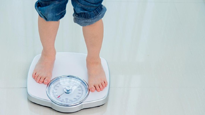 Boy measures weight on a weight scale.