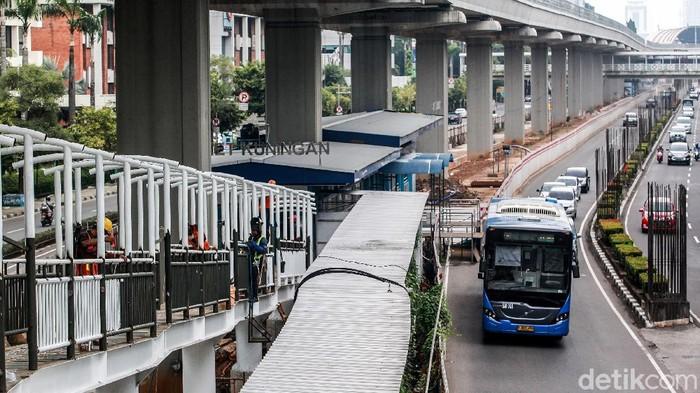 Para pekerja menyelesaikan proses konstruksi jembatan pejalan kaki di Halte Busway Karet Kuningan, Jl Rasuna Said, Jakarta, Sabtu (6/3/2021).