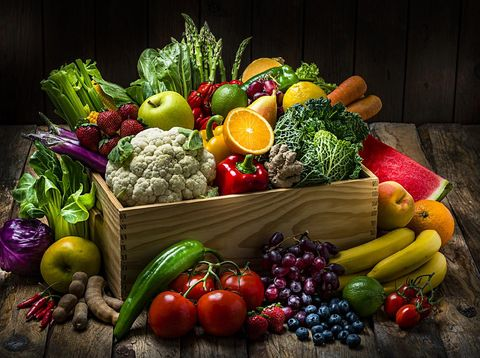Healthy food: large selection of fresh organic multicolored vegetables in a crate shot on dark wooden table. Fruits and vegetables included in the composition are watermelon, oranges,lime, lemons, banana,grape, strawberries, apples, pears, blueberries, tamarind, kale, tomatoes, squash, asparagus, celery, eggplant, carrots, lettuce, edible mushrooms, bell peppers, cauliflower, ginger, corn, bok choy, raw potatoes, chili peppers among others. High resolution studio digital capture taken with Sony A7rII and Sony FE 90mm f2.8 macro G OSS lens