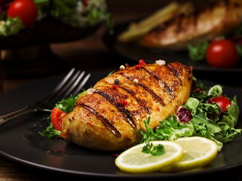 grilled chicken breast with green salad and french fries on a black plate.