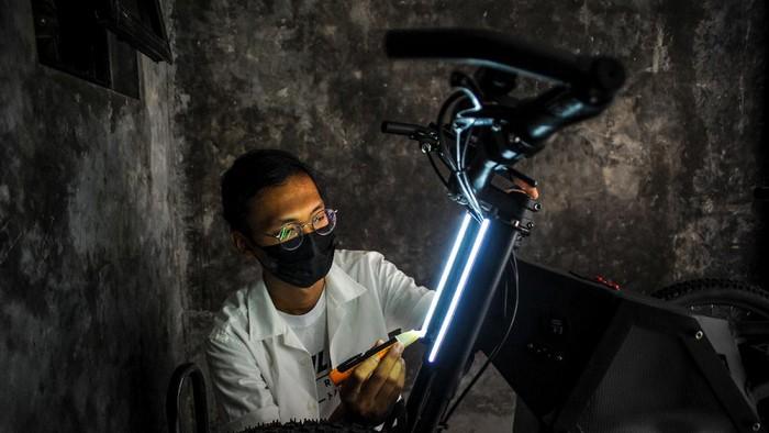 Seorang pelajar, Taufiqul Rahman (19) menghidupkan sepeda listrik buatannya dengan menggunakan jari nya di Sariwates, Bandung, Jawa Barat, Senin (8/3/2021). Sepeda listrik buatan Taufiqul Rahman yang diberi nama Vector tersebut memiliki kapasitas 1.000 watt dan mampu bertahan selama 4 jam dengan maksimal kecepatan hingga 60 kilometer per jam serta memiliki teknologi yang canggih seperti menghidupkan mesin dengan