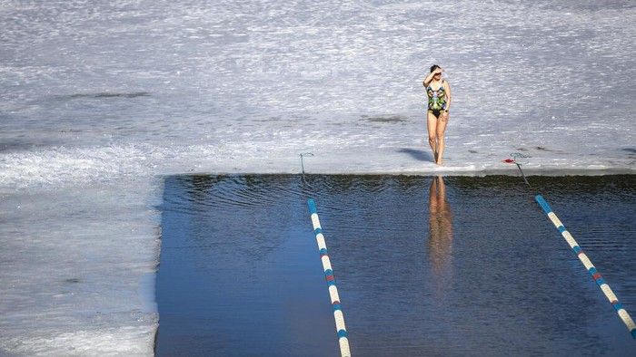 A woman celebrates after the finish during a winter swimming competition in the 25 meters long ice hole in a lake near Vilnius, Lithuania, Saturday, March 6, 2021. The water temperature was 3 degrees Celsius (37.4 degrees Fahrenheit), the air was -3 degrees Celsius (26,6 degrees Fahrenheit). (AP Photo/Mindaugas Kulbis)