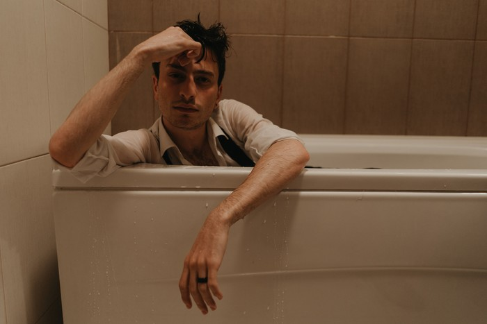 Young depressed male having anxiety alone himself in the bathroom. Young teenager male having breakdown alone.