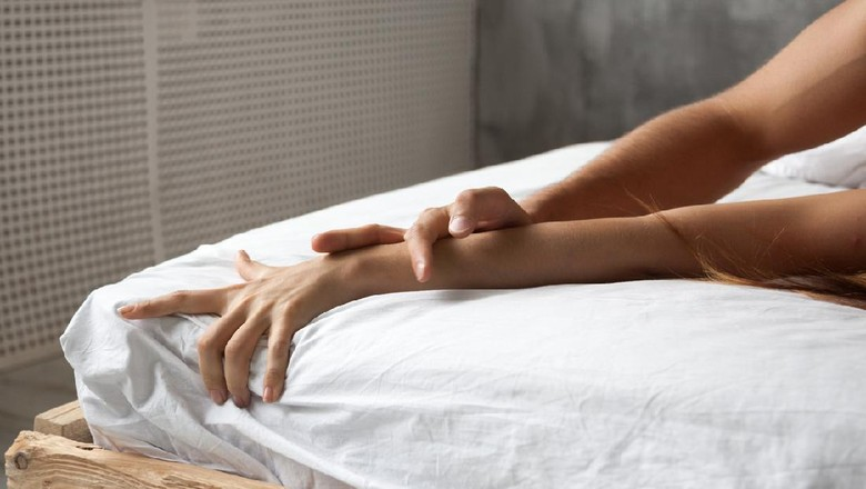 Close up of couple hands lie on bed relaxing in bedroom, lovers have intense sex or making love feeling orgasm and satisfaction, boyfriend and girlfriend enjoy foreplay on white sheets in the morning