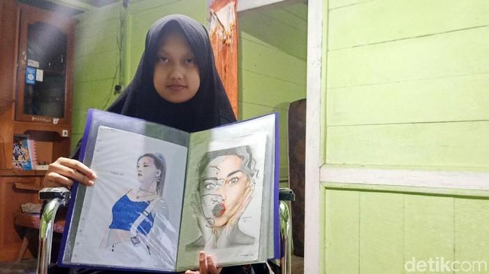 Eprisa Nova Rahmawati yang biasa dipanggil Rahma menunjukkan lukisannya di rumah sederhananya di Desa Penusupan, Kecamatan Pejawaran, Kabupaten Banjarnegara, Jawa Tengah, Selasa (9/3/2021).