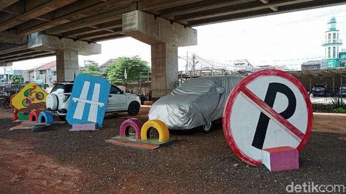 Suasana taman pilar jati yang kini digunakan menjadi parkir liar di Kolong Tol Becakayu, Cipinang Melayu, Jakarta Timur, Selasa (9/3/2021). Taman yang dibuat atas inisiatif lurah dan petugas PPSU ini kini tampak digunakan untuk parkir liar oleh warga.
