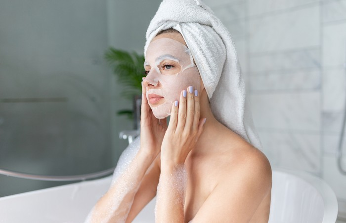 Beautiful young woman sitting in bathtub with sheet mask on face. Close up portrait of pretty girl in bath towel on head and doing beauty treatment. Home bathroom interior. Spa procedure. Skincare
