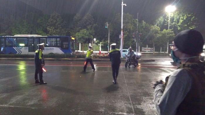 Polisi filter kendaraan di kawasan Bundaran Senayan, Jakarta Selatan malam ini.