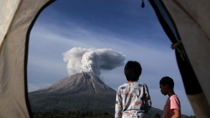 Campers are seen from the opening of a tent as they watch Mount Sinabung erupting in Karo, North Sumatra, Indonesia, Thursday, March 11, 2021. The 2,600-meter (8,530-feet) volcano unleashed an avalanche of searing gas clouds flowing down its slopes during eruption on Thursday. No casualties were reported. (AP Photo/Binsar Bakkara)