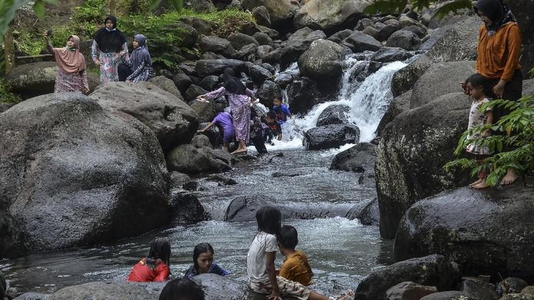 Pengunjung bermain di Sungai Cireong, Desa Sukaresik, Kecamatan Sindangkasih, Kabupaten Ciamis, Jawa Barat, Kamis (11/3/2021). Para pengunjung mengisi libur Isra Miraj dengan mengunjungi wisata alam Cireong yang dikelola Badan Usaha Milik Desa (BUMDes) dan Karang Taruna setempat, yang menyuguhkan daya tarik air sungai yang masih jernih dari kaki Gunung Sawal dan hamparan bebatuan besar. ANTARA FOTO/Adeng Bustomi/aww.