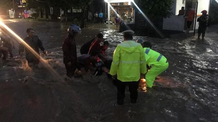 Banjir melanda Jalan Sukowati Magetan. Derasnya arus banjir membuat 3 motor sampai terseret.