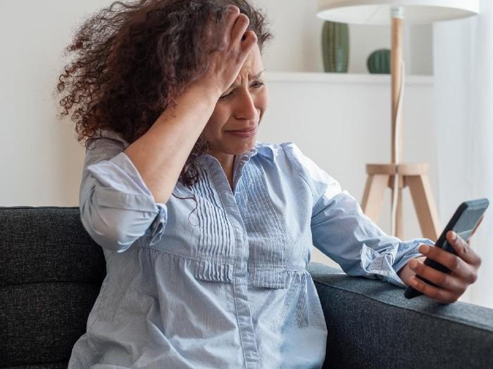 Sad black woman reading bad news on mobile phone