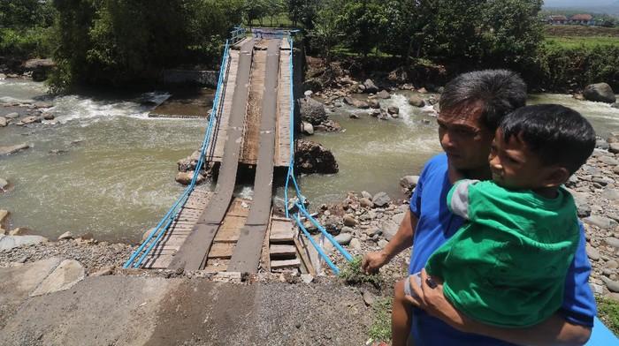 Suasana jembatan rusak di Desa Kweden, Nganjuk, Jawa Timur, Sabtu (13/3/2021). Jembatan yang menjadi akses utama antar desa di wilayah tersebut ambrol karena tergerus derasnya aliran sungai Kedungbocah saat banjir. ANTARA FOTO/Prasetia Fauzani/foc.