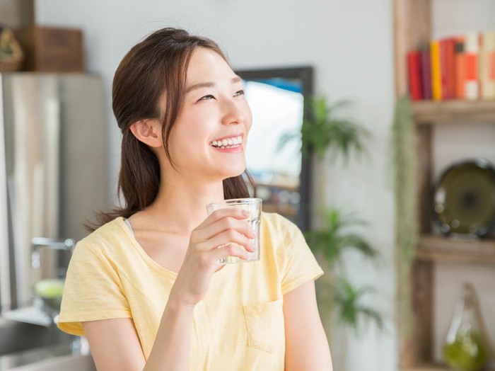 young attractive asian woman who drinks water in a kitchen