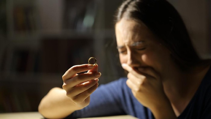 Sad wife crying hoding wedding ring in the night at home