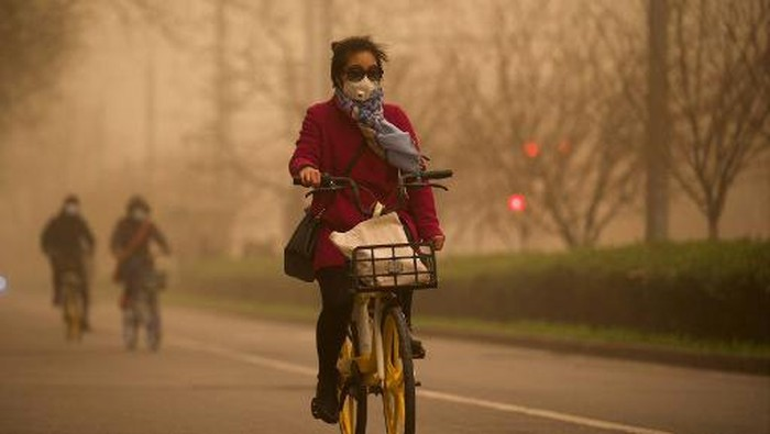 A woman cycles along a street during a sandstorm in Beijing on March 15, 2021. (Photo by Noel Celis / AFP)