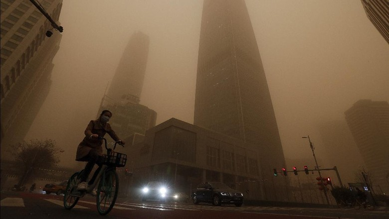 A cyclist and motorists move past office buildings amid a sandstorm during the morning rush hour in the central business district in Beijing, Monday, March 15, 2021. The sandstorm brought a tinted haze to Beijings skies and sent air quality indices soaring on Monday. (AP Photo/Andy Wong)