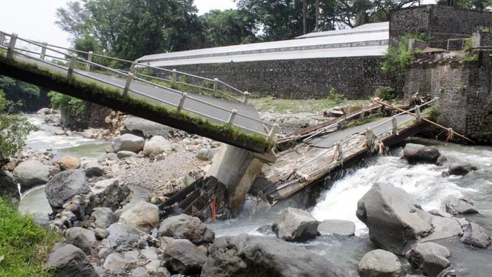 Jembatan penghubung antar desa ambrol di Desa Sumbersuko, Gempol, Pasuruan, Jawa Timur, Senin (15/3/2021). Jembatan sepanjang 21 meter yang menjadi akses utama antar desa di wilayah tersebut ambrol diterjang banjir akibat luapan Sungai Kaliputih, pascahujan deras. ANTARA FOTO/Umarul Faruq/hp.