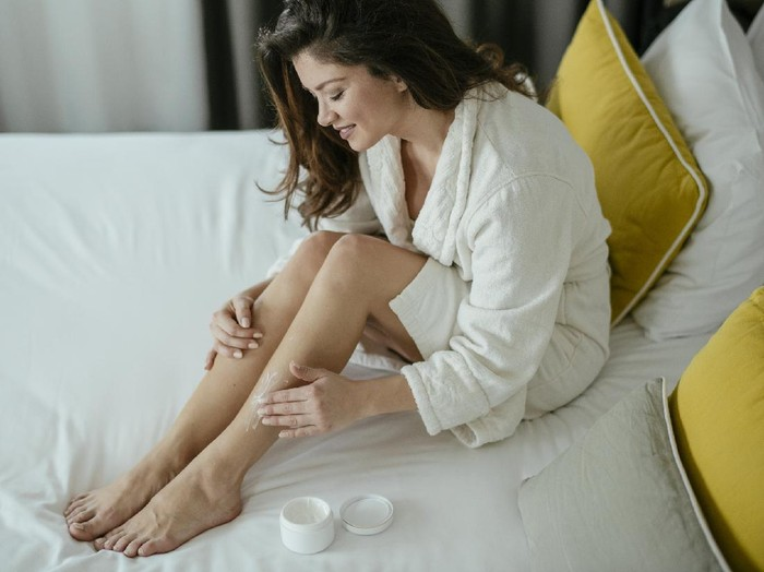 Woman, Skin care, Cream, Bedroom. Woman taking care of her legs at home.  Shallow DOF. Developed from RAW; retouched with special care and attention; Small amount of grain added for best final impression. 16 bit Adobe RGB color profile.
