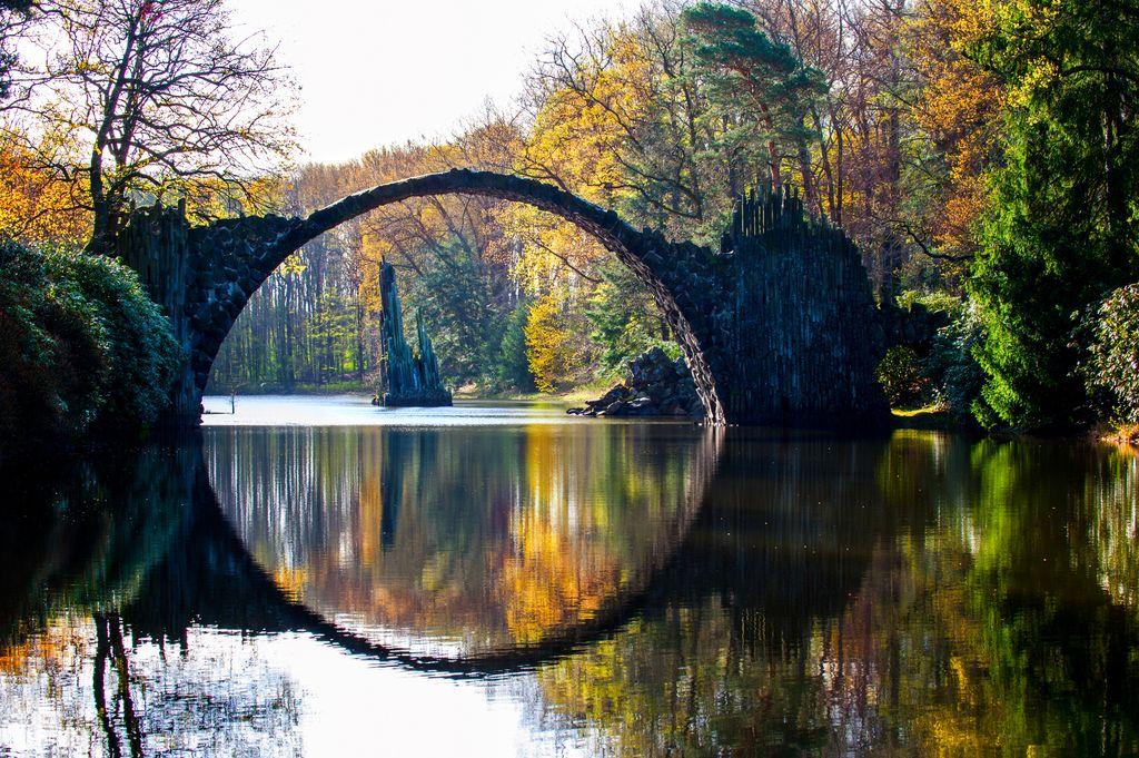 Spectacular autumn season in Azalea and Rhododendron Park Kromlau. Rakotz Bridge, Rakotzbrucke Devil's Bridge in Kromlau, Saxony, Germany. Horizontal outdoor colorful image