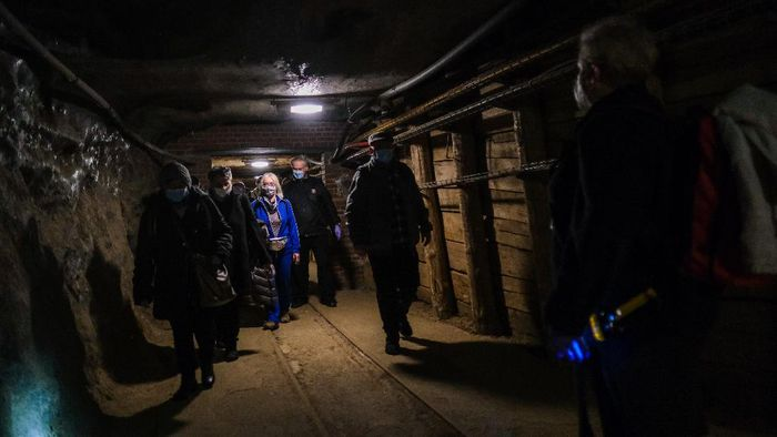 WIELICZKA, POLAND - MARCH 12: COVID-19 recovered patients wear protective face masks and walk through tunnels inside the the Wieliczka health resort  on March 12, 2021 in Wieliczka, Poland. The Wieliczka health resort complex at the Wieliczka salt mine, is a UNESCO World Heritage site. The health resort complex, located 135 meters underground, is hosting a rehabilitation program for people who contracted and largely recovered from Covid-19, but who still experience negative health effects like fatigue, lower exercise tolerance, low mood or lack of energy.  Polands only underground health resort is known for its unique microclimate, which has been used for years to treat chronic respiratory diseases. The purity of the air, due to the high concentration of salt aerosol and the ionization and increased atmospheric pressure, are said to have a positive impact on the efficacy of pulmonary rehabilitation. (Photo by Omar Marques/Getty Images)