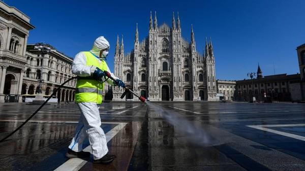 Ini adalah foto penyemprotan disenfektan di salah satu tujuan populer di Milan, Piazza Duomo. Penyemprotan dilakukan saat Italia mengunci negaranya di awal kasus pertama mereka. (Piero Cruciatti/AFP/Getty Images)