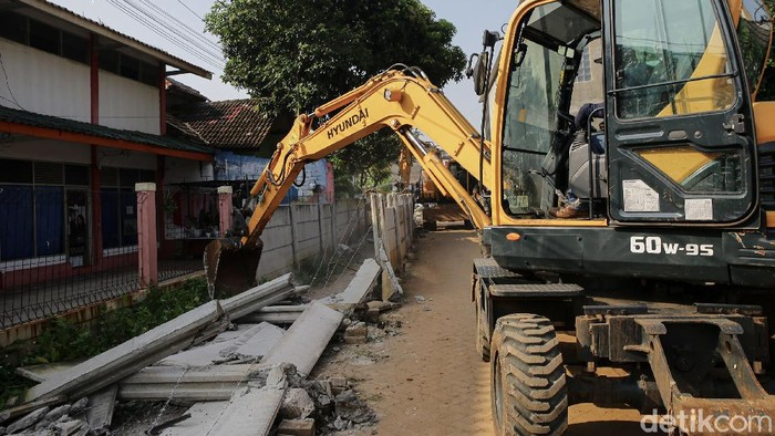 Tembok yang menutup akses keluar-masuk rumah Hadiyanti (60), warga Ciledug, Kota Tangerang, dirobohkan. Ekskavator pun diturunkan.