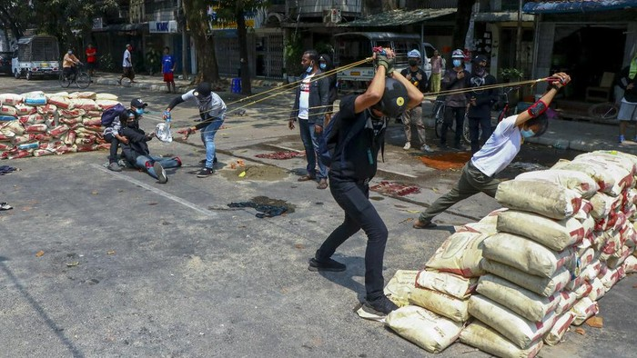 Anti-coup protesters test an improvised weapon they have made to fight with armed Myanmar security forces in Yangon, Myanmar Wednesday, March 17, 2021. (AP Photo)