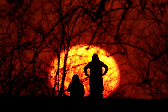 Girls are silhouetted against the setting sun as they enjoy a spring-like day Saturday, March 6, 2021, in Kansas City, Mo.