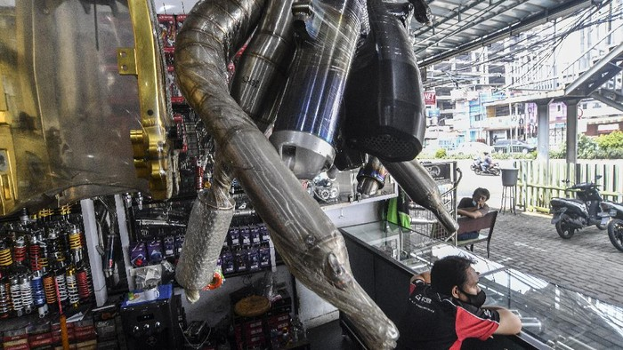 Penjual knalpot dan aksesori modifikasi sepeda motor melayani calon pembeli di kawasan Kampung Melayu, Jakarta, Jumat (19/3/2021). Maraknya razia knalpot racing atau bising oleh pihak kepolisian berdampak pada turunnya penjualan knalpot aftermarket (suku cadang pengganti yang dibuat oleh perusahaan selain produsen asli kendaraan) yang memiliki suara bising. ANTARA FOTO/Muhammad Adimaja/foc.