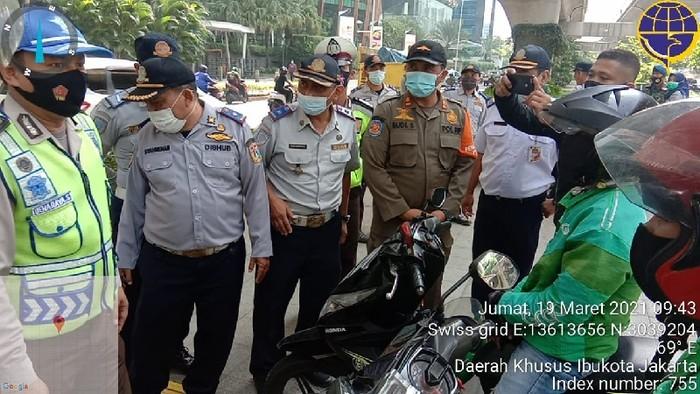 Dishub DKI gebah pemotor yang putar balik di trotoar depan Mal Kuningan City, Jaksel. (Dok situs CRM Jakarta Smart City)