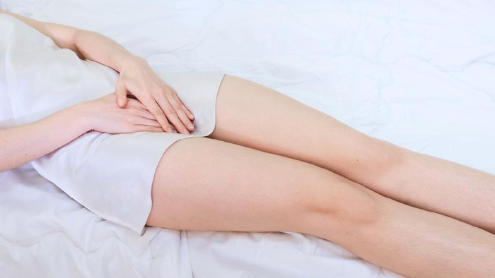 woman wearing white Sleepwear lying on bed . Female holding hand to spot of vagina-ache. Concept photo Penis pain.Health care concept,Soft focus