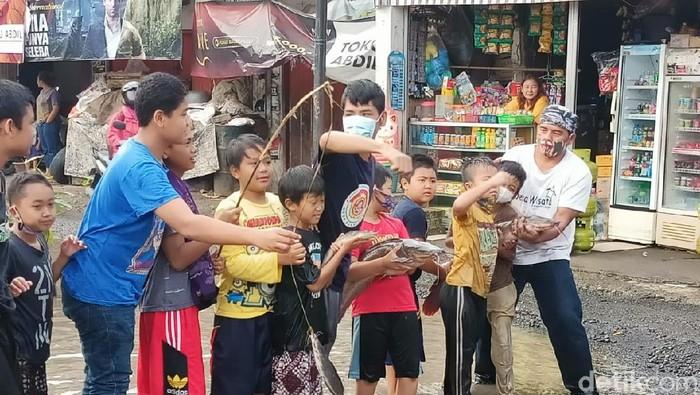 Sebagai bentuk protes, warga Bogor memancing ikan di kubangan jalan rusak