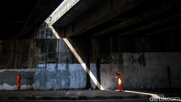 Para petugas PPSU Kelurahan Bintaro mengecat dinding kolong tol di Jl Bintaro Permai Raya, Jakarta Selatan, Sabtu (20/3/2021). Cat putih tersebut akan menjadi cat dasar atau semacam kanvas untuk pembuatan lukisan mural. Sebelumnya, dinding kolong tol ini banyak terdapat coretan, grafiti dan poster iklan.